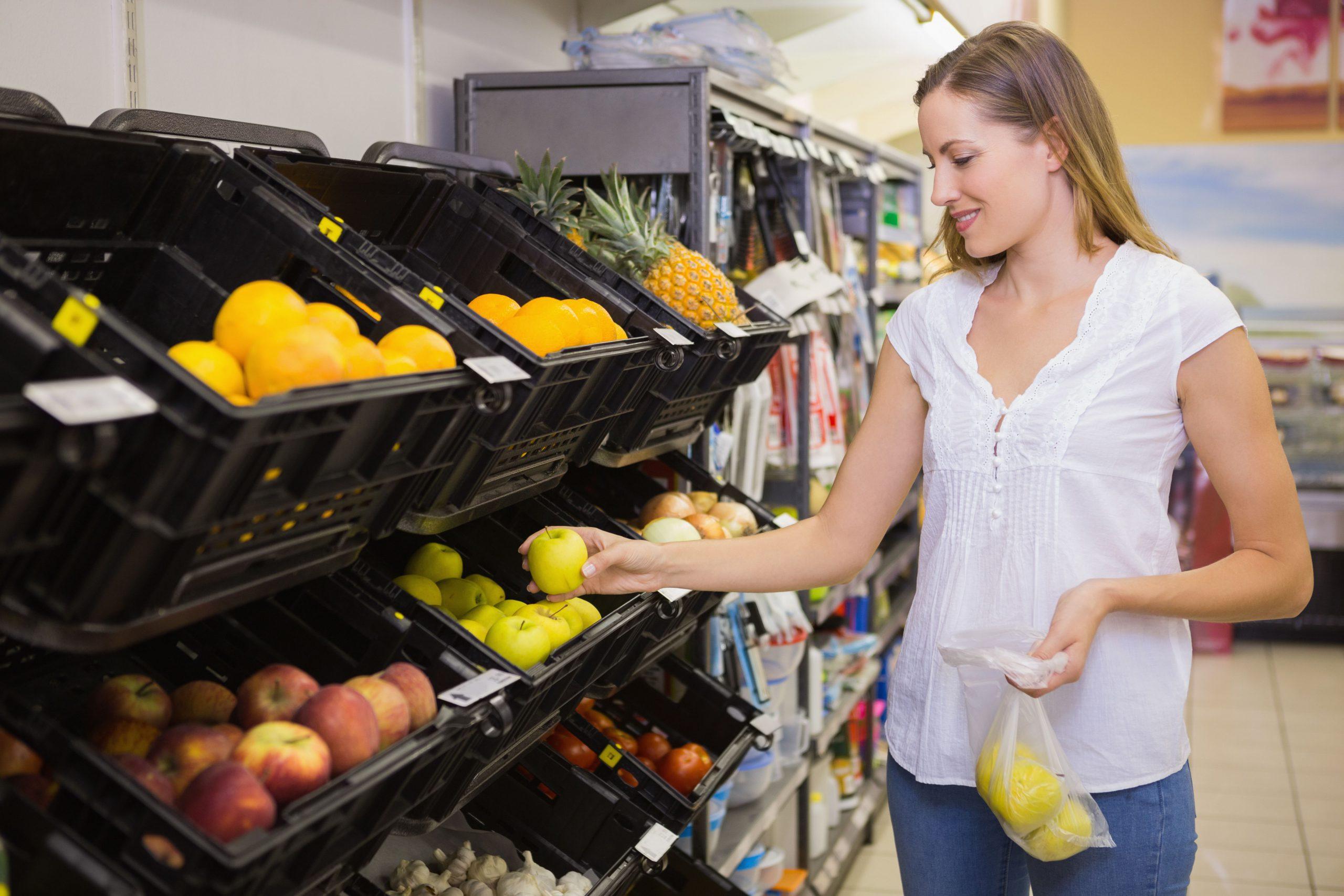 Frau am Obstregal im Supermarkt