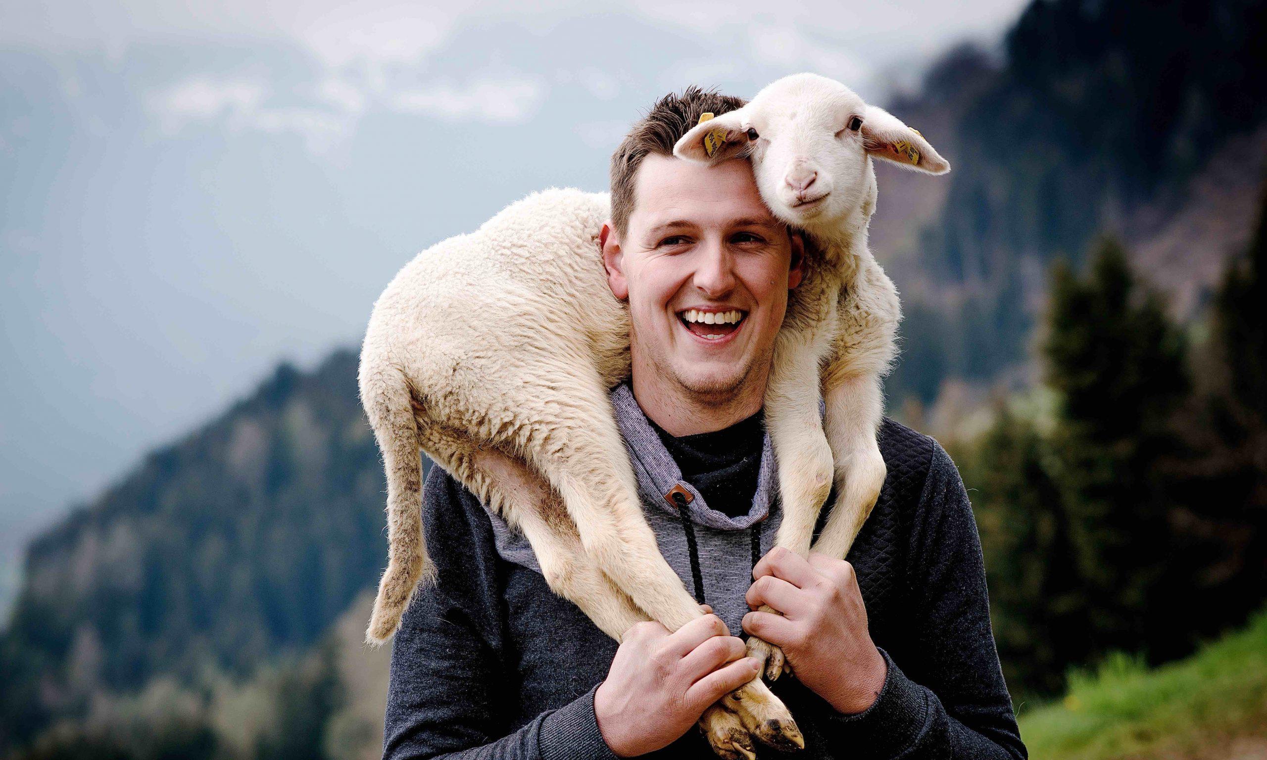 Matthias Kollnig mit einem Lamm auf seinen Schultern