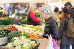 Frau kauft Gemüse auf dem lokalen Lebensmittelmarkt