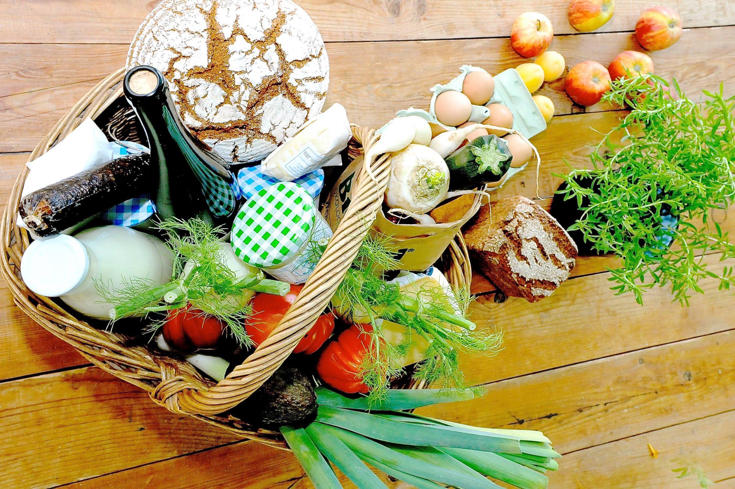 Korb mit Lebensmitteln wie Brot, Milch, Gemüse, Eier