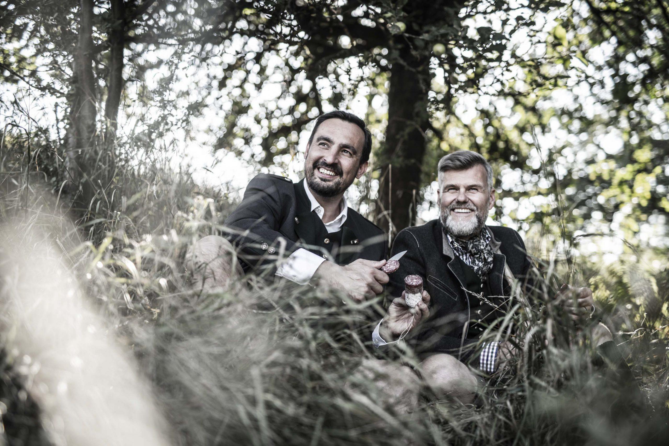 Zwei Jäger sitzen im Gras und essen eine Salami