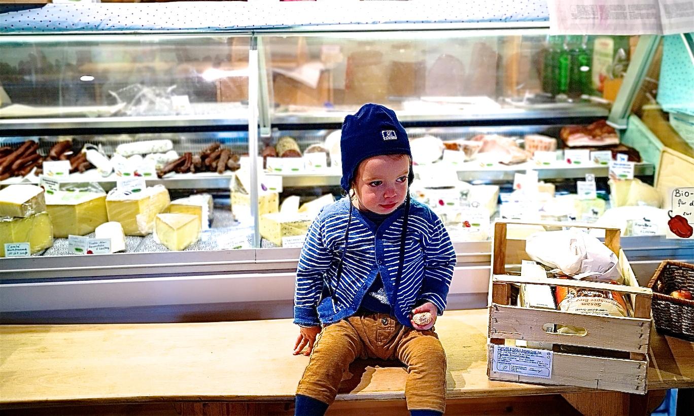 Kleiner Junge vor dem Käseregal