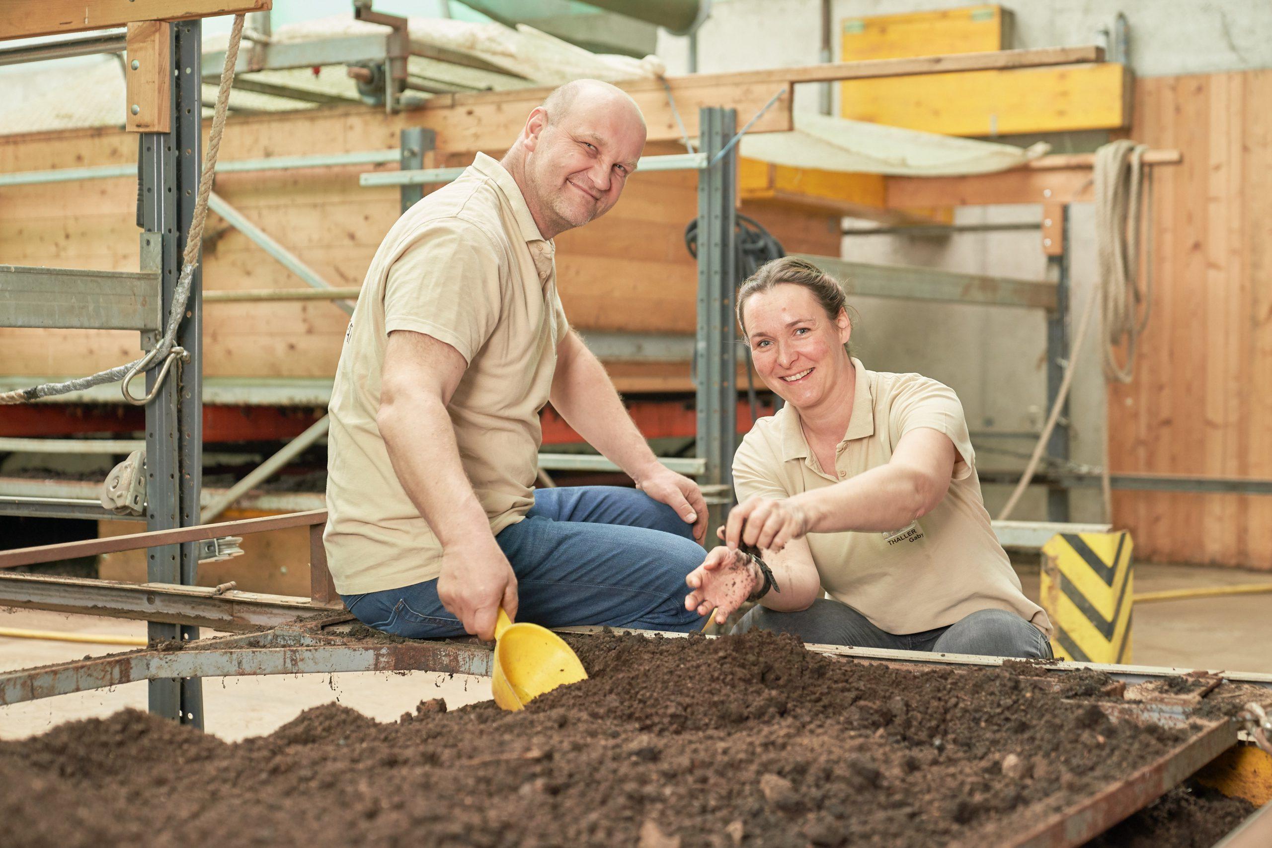 Herr und Frau Thaller vor einer Erdkiste mit einem Kompostwurf