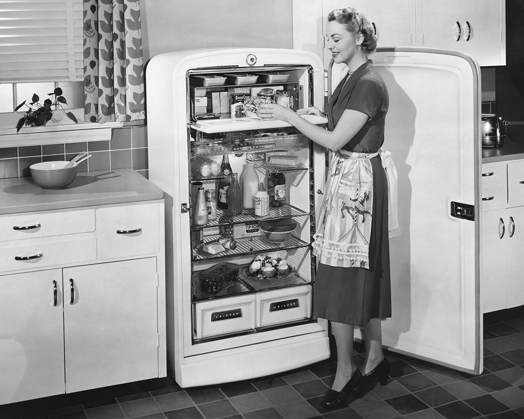 Hausfrau vor dem geöffneten Kühlschrank