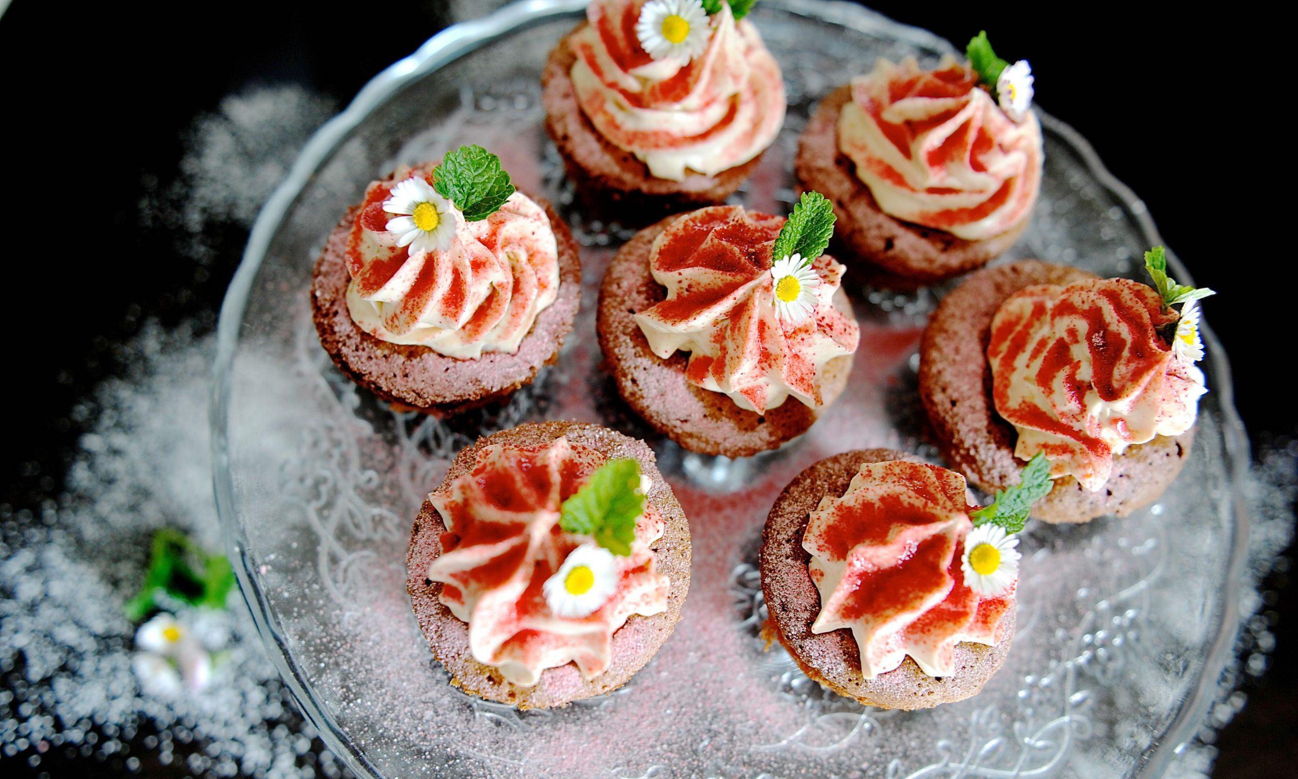 Cupcakes mit rotem Himbeerzucker und Gänseblümchen