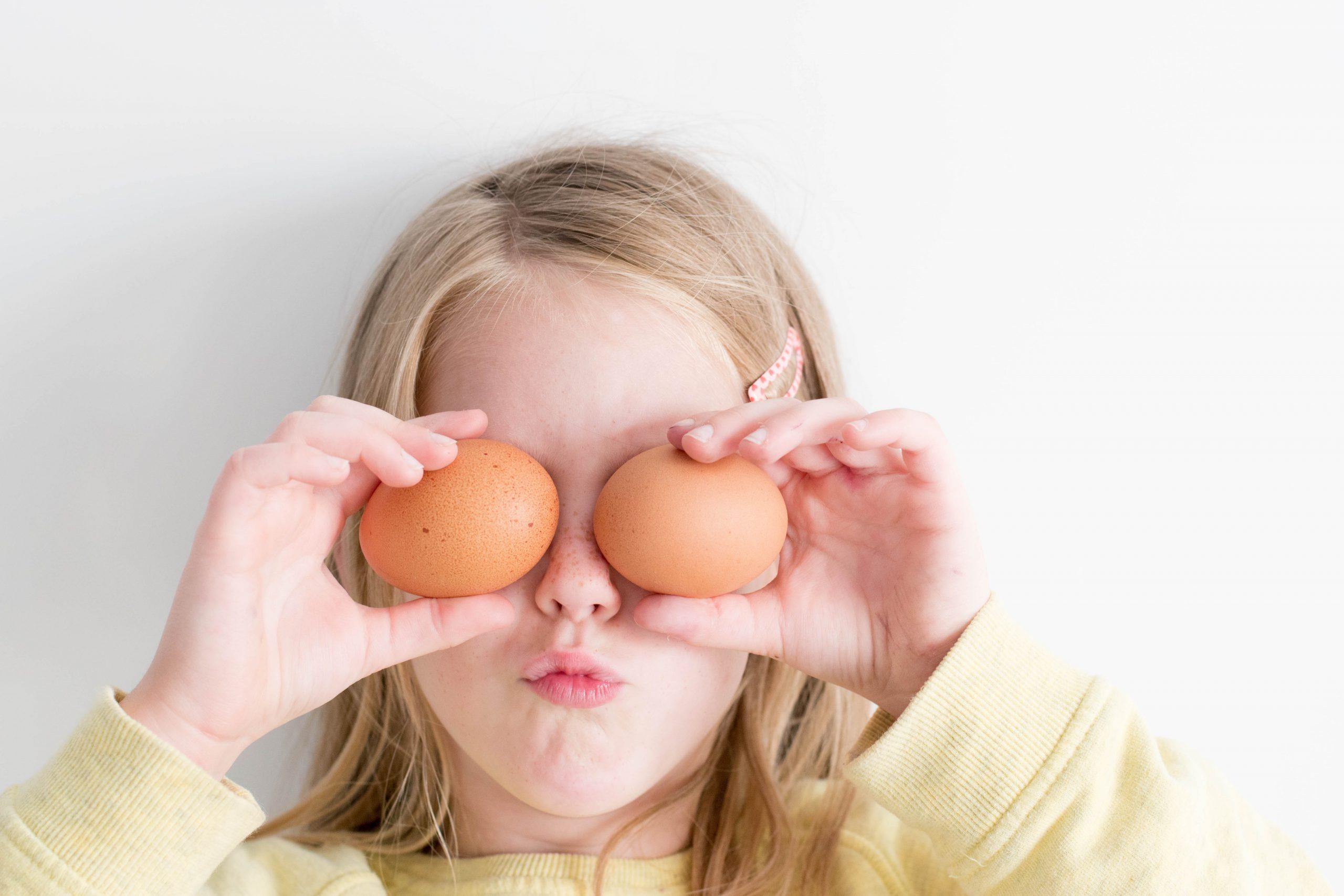 Mädchen hält sich Eier vor die Augen