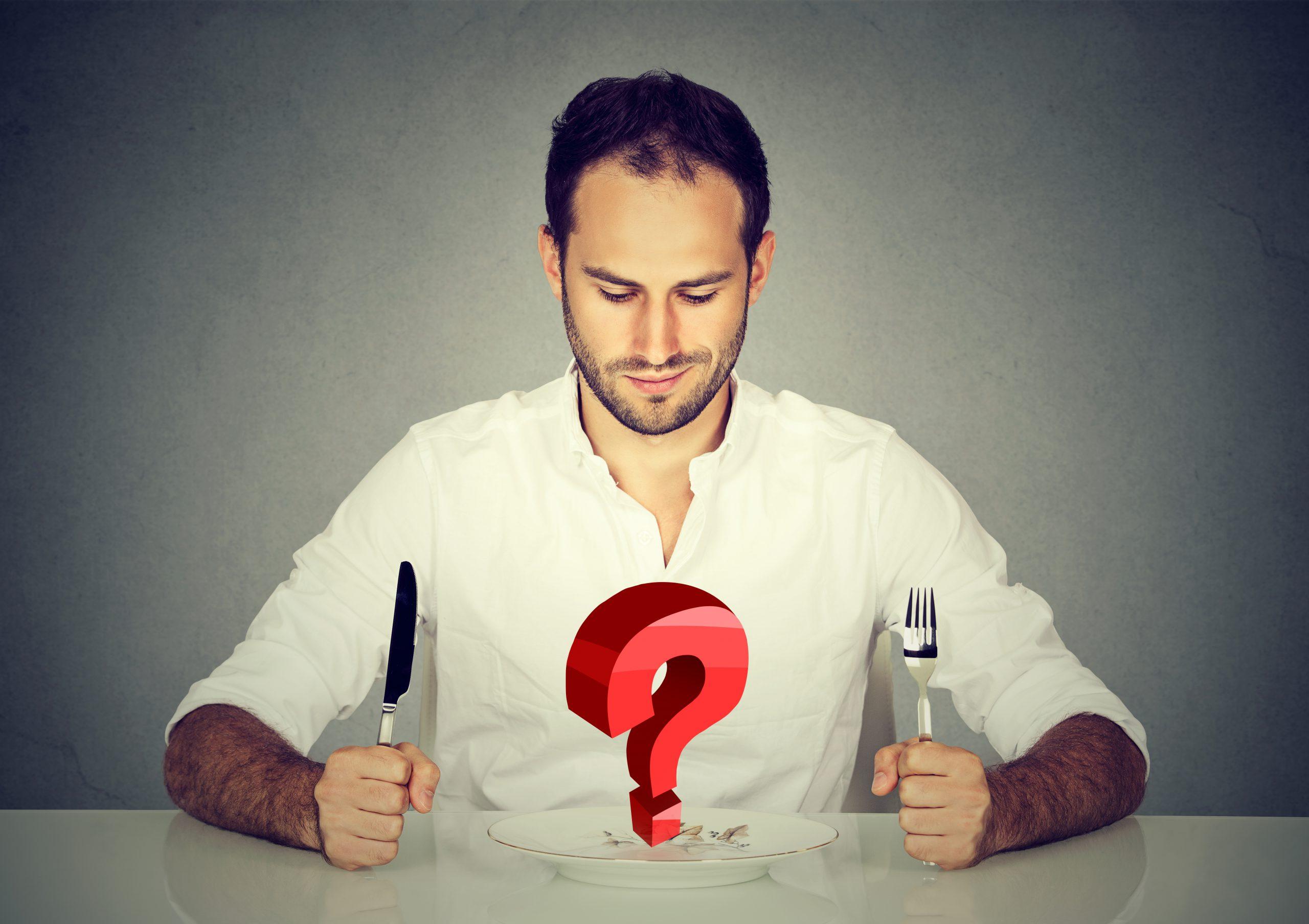 Mann mit Gabel und Messer sitzt am Tisch und blickt auf Teller mit großer roter Frage