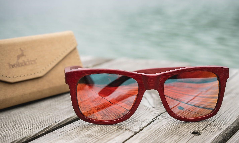 Rote Holzsonnenbrille auf einem Steg mit Wasser
