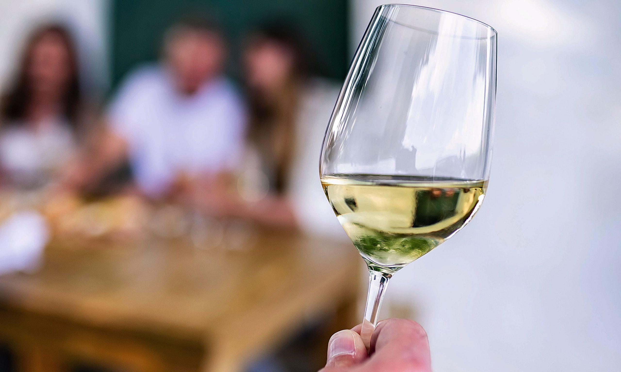 Weinglas mit Menschen im Hintergrund