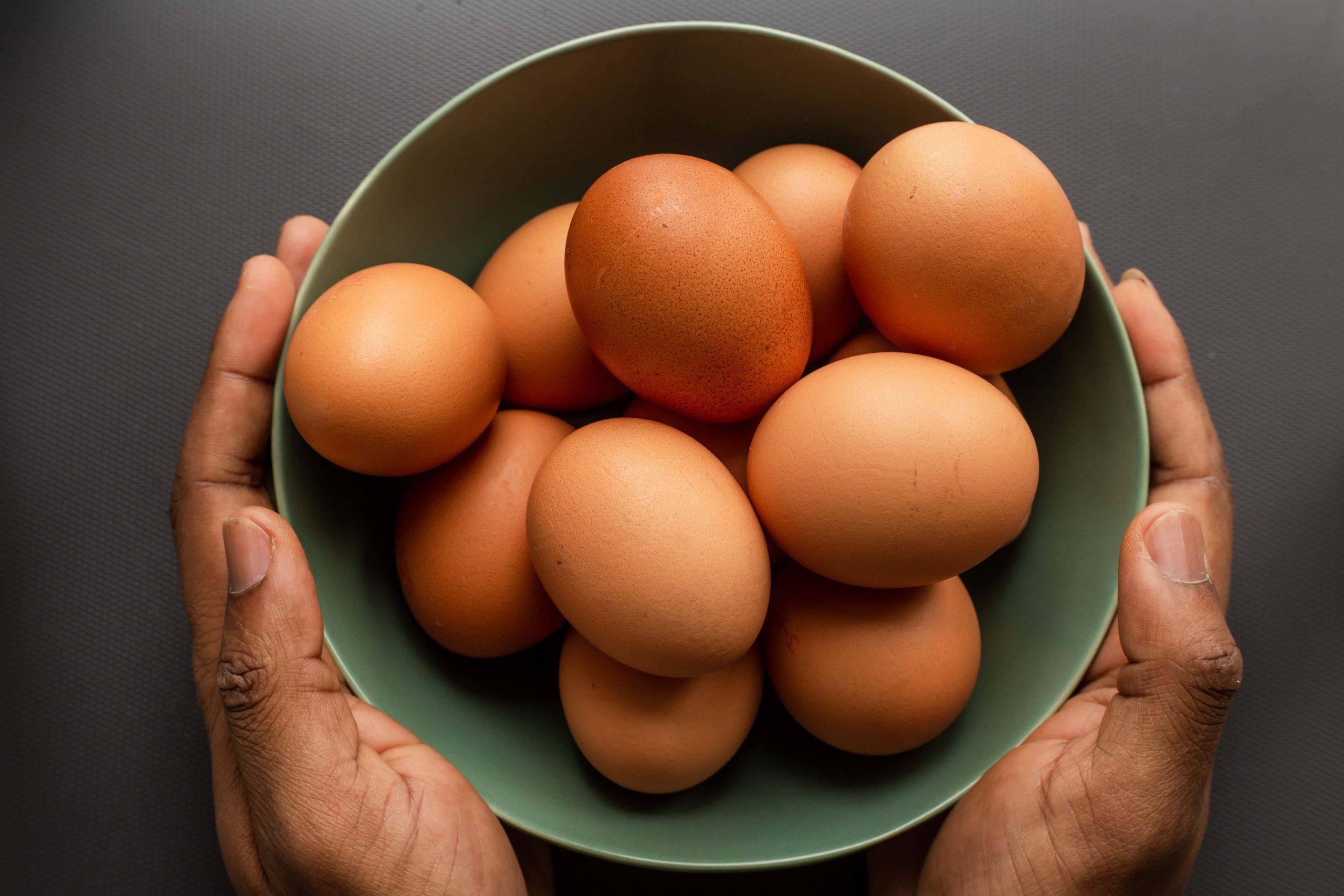 Hände halten eine Schüssel mit Eiern