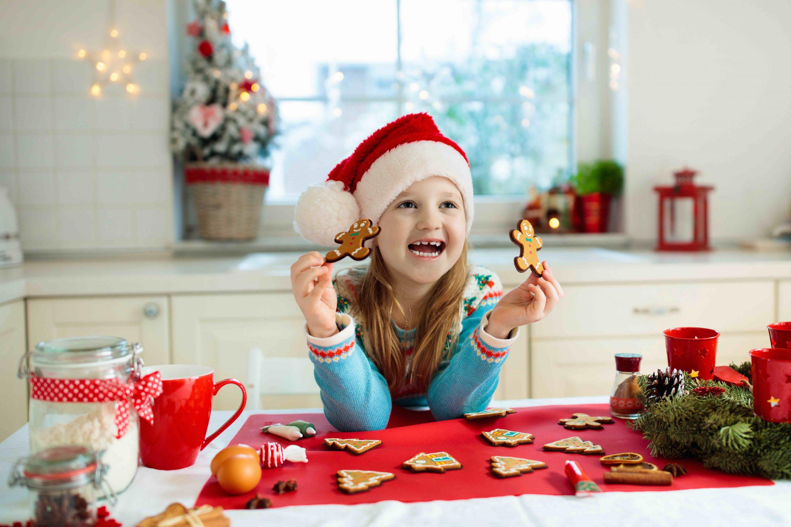 Kinder backen Weihnachtsplätzchen. Kind mit Weihnachtsmütze kocht, dekoriert Lebkuchenmann für Weihnachtsfeier. Familie bereitet an einem verschneiten Wintertag Süßigkeiten in weißer Küche mit Weihnachtsbaum zu.