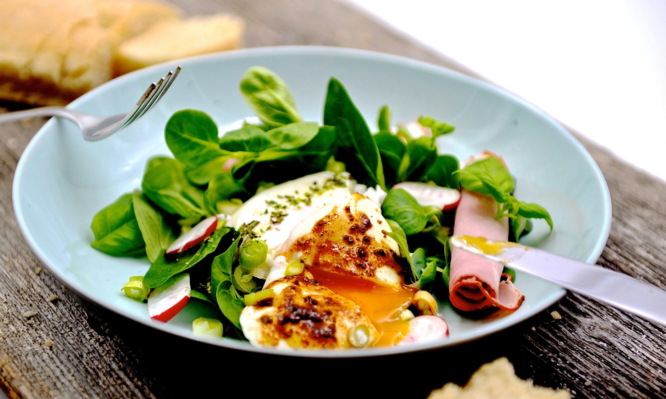 Salat mit pochiertem Ei und Schinken