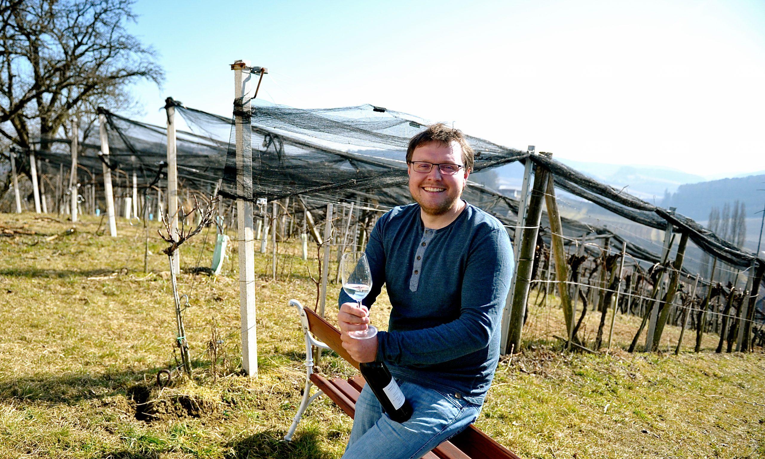 Matthias Höfler mit Glas Wein und Flasche im Weingarten