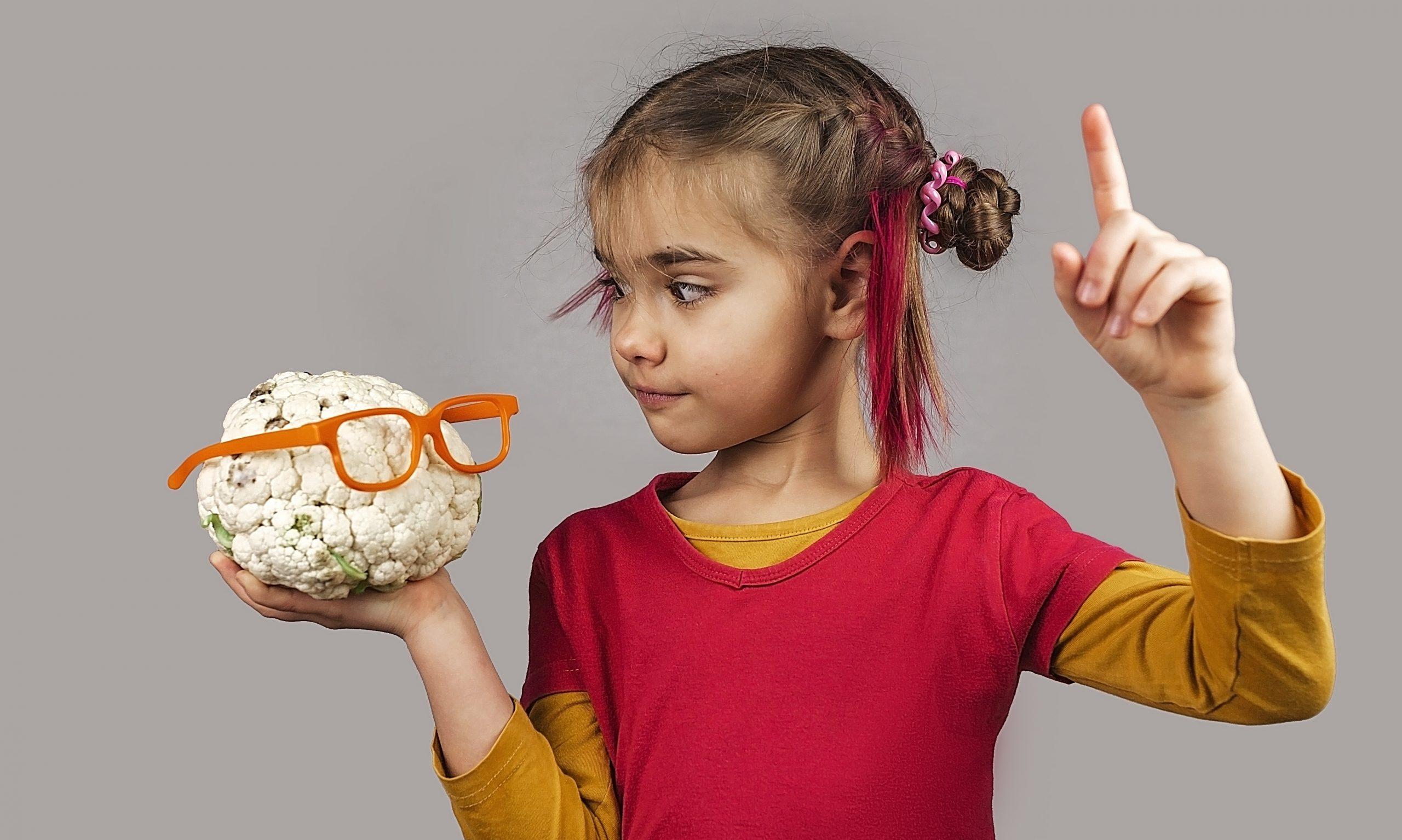 Ausgeflipptes Kind hält unförmiges Obst und Gemüse in falscher Farbe,