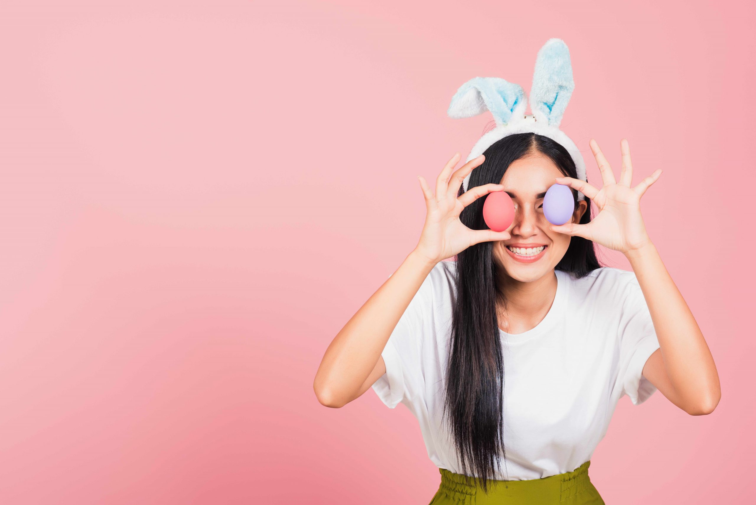 woman smiling wearing rabbit ears holding colorful Easter eggs front eyes