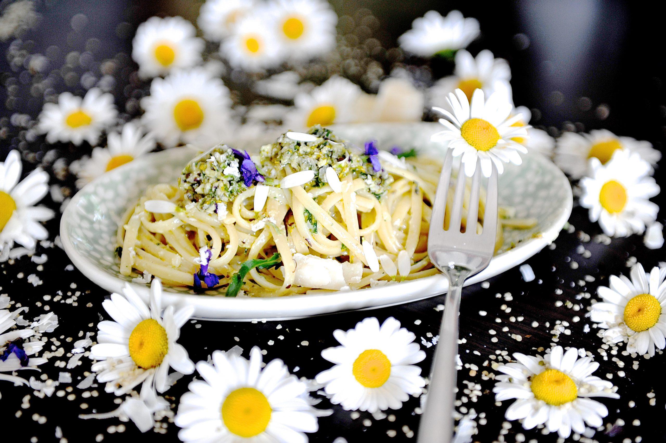 Margaritenblüten und ein Teller mit Pasta