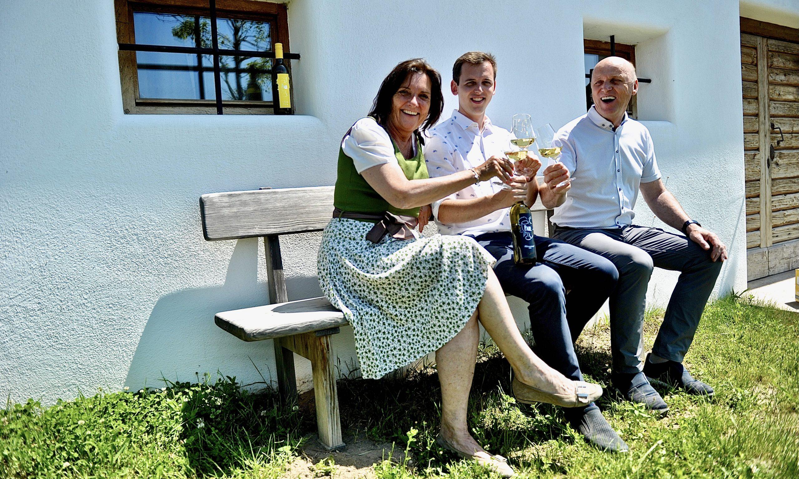 Eine Frau und zwei Männer auf einer Bank mit Weingläsern, zuprosten