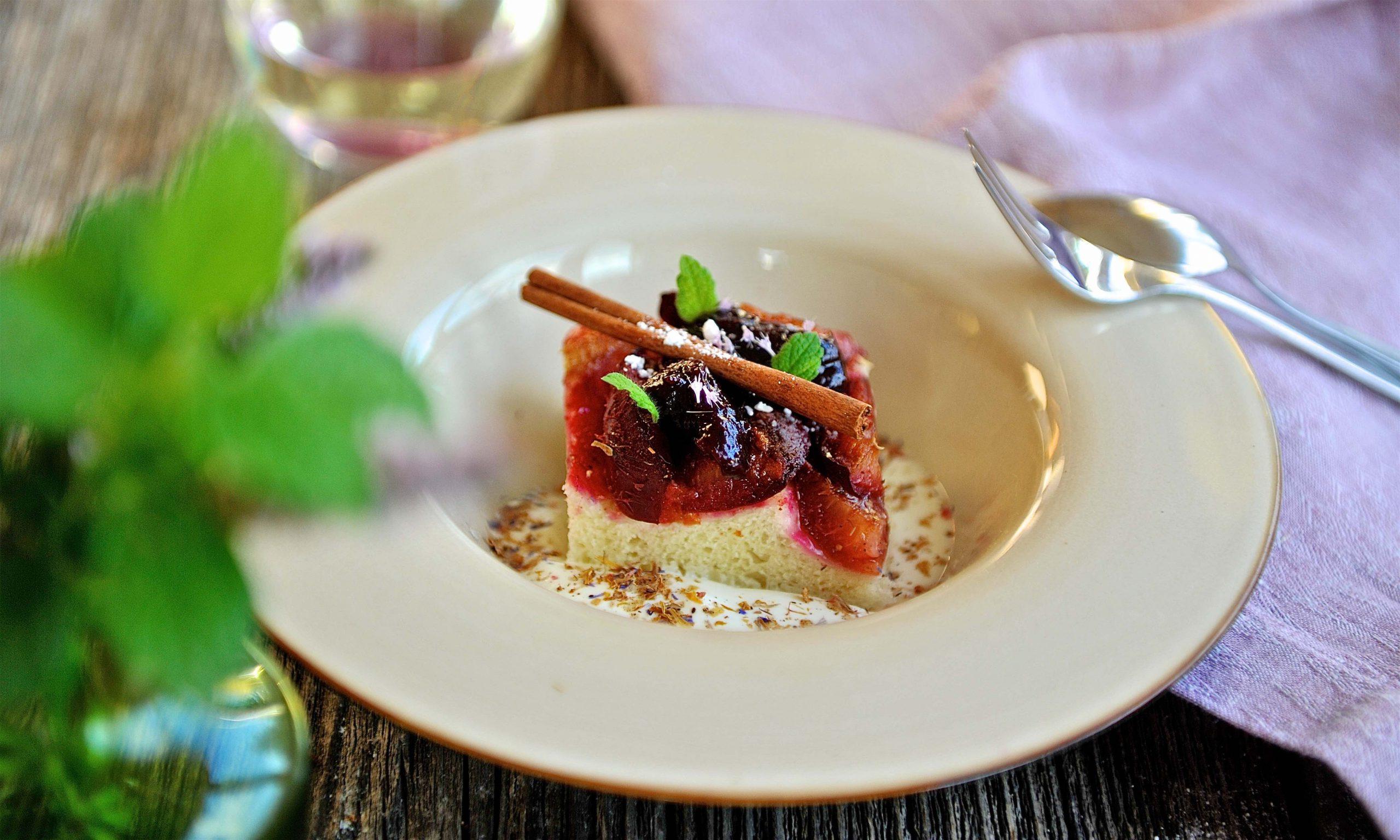 Kuchen mit Zwetschken in einem tiefen Teller, Serviette, Melisse