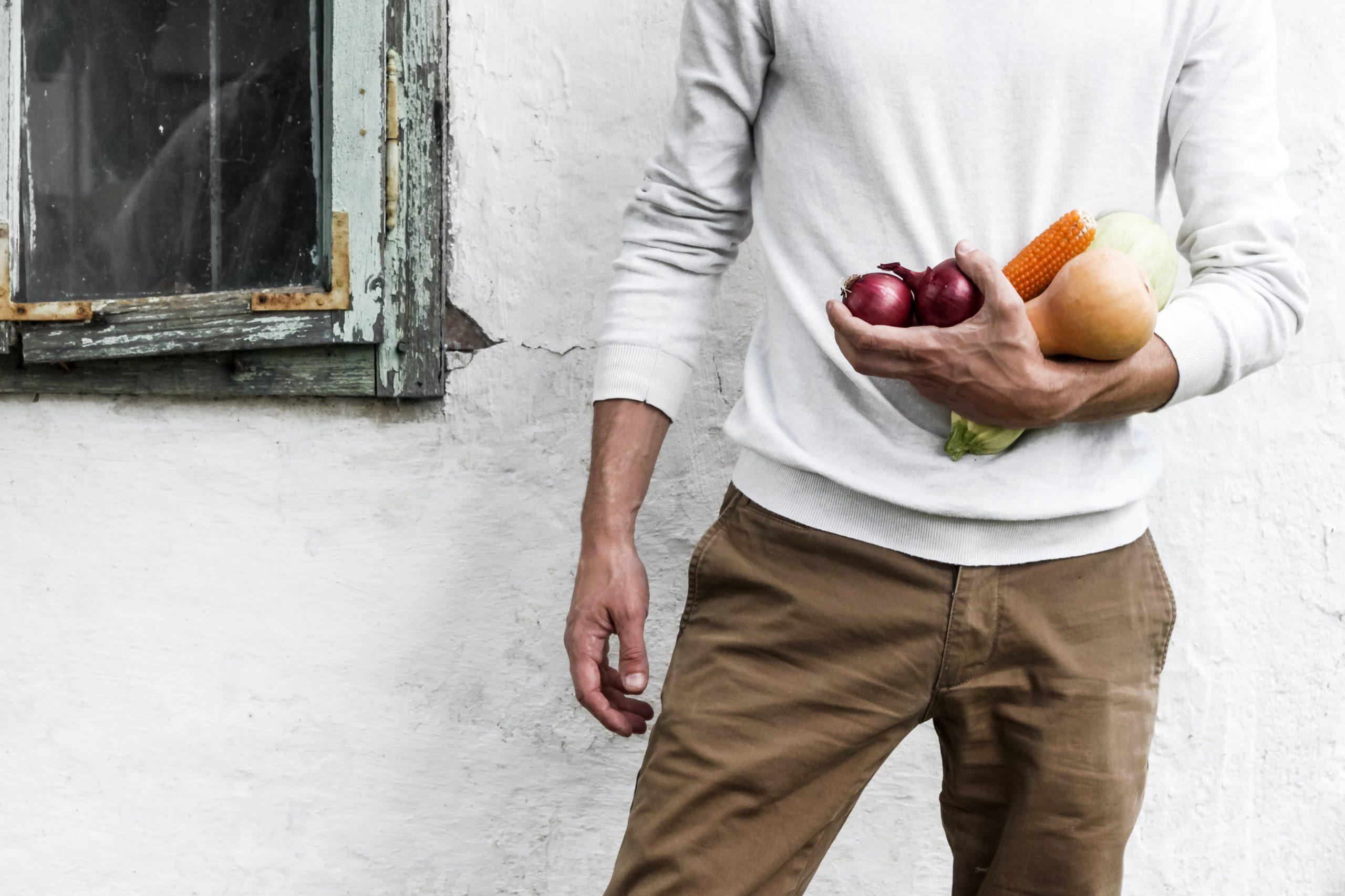 Mann hält Gemüse am Arm
