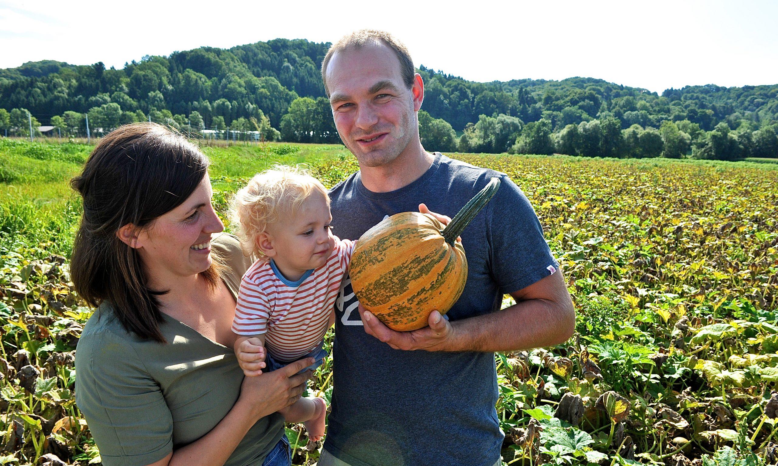 Familie mit Kleinkind am Kürbisacker